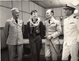 Amelia Earhart with three military men