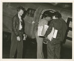Amelia Earhart and men loading her plane
