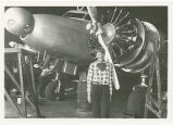 Amelia Earhart standing by a propeller of her Electra