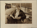 Amelia Earhart, seated in library, with book