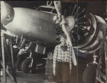 Earhart standing in front of Electra's left propeller