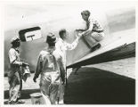 Amelia Earhart being assisted off her plane