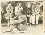 Amelia Earhart and others seated on a car