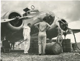 Amelia Earhart inspecting a steel fuel drum