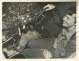 Amelia Earhart sitting in the cockpit of her Lockheed Electra