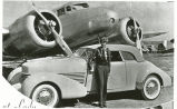 Amelia Earhart standing in front of her car and airplane