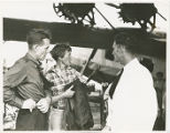 Amelia Earhart conversing with Fred Noonan and E. Henry Linam