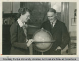 Amelia Earhart and President Elliott with a globe