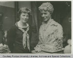 Amelia Earhart standing next to a sculpted clay bust