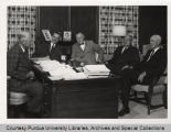Fred Hovde and other administrators seated around desk