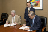 Provost Randy Woodson signing memorandum with Da Hsuan Feng as Michael Lai looks on