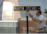 Worker installing new street sign
