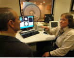 Two people talking with magnetic imaging machine in background