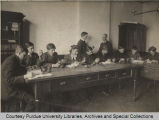 Students seated at table examining vegetables