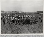 Group of men planting seed with tractor