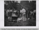 Men standing around a cooking pot