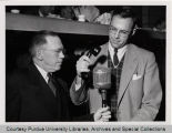 Chet Biddle and unidentified man in front of microphone