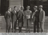 President Elliott and others standing with man with egg basket