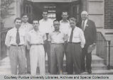 Group of men posing outside campus building