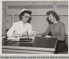 Mary R. Maginsky seated at desk, talking with woman