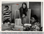 Woman and students working with egg cartons