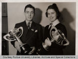 Clifford Breeden and Helen Michael standing together, holding trophies