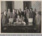 Men gathered around Governor Craig, seated at desk