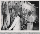 Two men inspecting meat carcasses