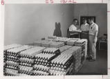 Men standing near egg cartons