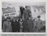 People standing in front of United Air Lines airplane