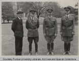 President Elliott and military personnel standing on campus