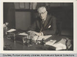 George Ade seated at desk