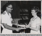 Mary K. McMunn being congratulated by rear admiral