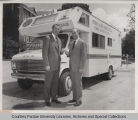 Two men standing in front of Purdue Alumni Association van