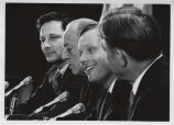 Neil Armstrong, seated, at press conference with three men