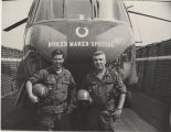 Purdue alumni in military uniforms in front of helicopter
