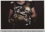Purdue football player holding Old Oaken Bucket