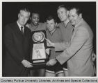 Purdue basketball players and coach with championship plaque
