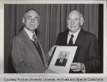 Dr. W. Malcolm Beeson standing with Dr. R.L. Kohls, holding portrait