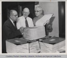 Three men inspecting Indiana DHIA records