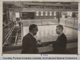 Professors Larry E. Higgins and E.J. Monke, standing in large room