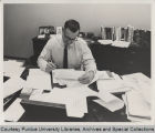 John Day, working at desk