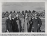 A.A. Potter, standing with President Hovde and others at football game