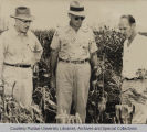 Glen Smith, standing with two men in corn field