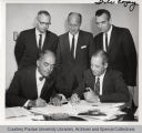 Gilbert Oakley and Shepherd Brooks seated, signing papers with others looking on