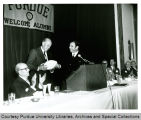 President Hovde receiving football from Hank Stram