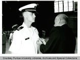 President F.L. Hovde pinning a medal