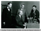 President F.L. Hovde and others around a piano