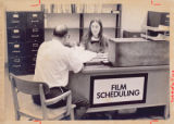 Patron and staff member at film scheduling desk in Purdue Libraries, Audio Visual center