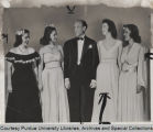 Earl Carroll standing with beauty contestants